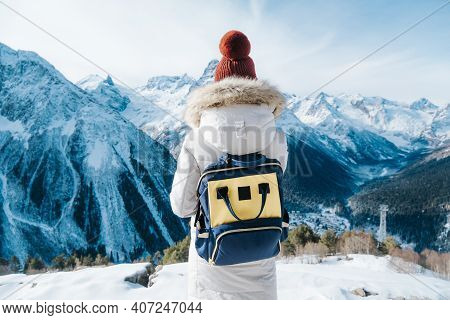 Girl Tourist Walks In The Mountains. Traveling With A Backpack.