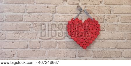 Red Heart Hanging On Brick Wall. Textured Symbol Of Love. Two Handmade Hearts On Light Brick Wall. C
