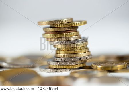 Metallic Euro Coins Standing In A Pile With Abundance Of Others Lying Around On