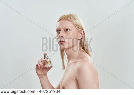 Young Caucasian Man With Long Blond Hair Holding Perfume Bottle While Standing On Light Background A