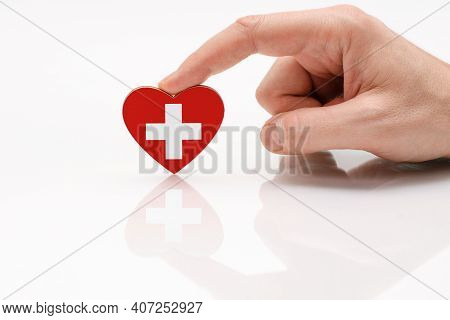 Love And Respect Switzerland. A Man's Hand Holds A Heart In The Shape Of The Switzerland Flag On A W