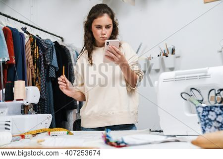 Thinking nice brunette girl seamstress using mobile phone while working in atelier