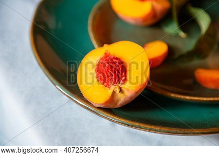 Peach In Half With Bone. Rustic Minimalist Food Peach Fruits With Leaves On Green Plate On Tableclot