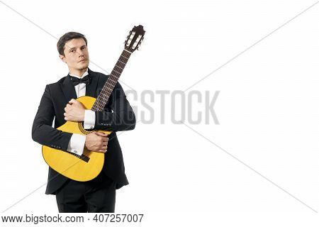 Handsome Young Man In Black Classic Suit With Bow Tie Posing With Classical Guitar In Studio On Whit