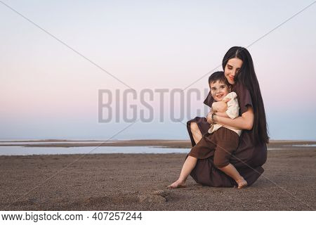 Happy Mother And Son Having Fun Together. Mother Gently Hugs Her Little Cute Son Outdoor. Family Loo