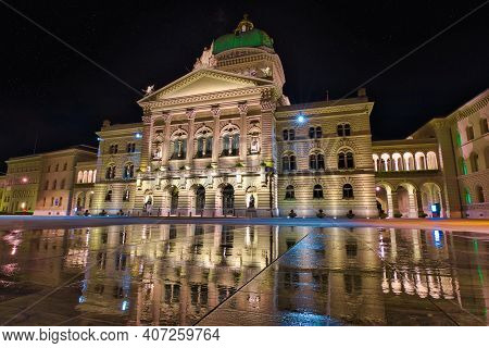 Federal Palace Facade In Bern, Switzerland Illuminated At Night. Swiss Parliament Building Reflectin