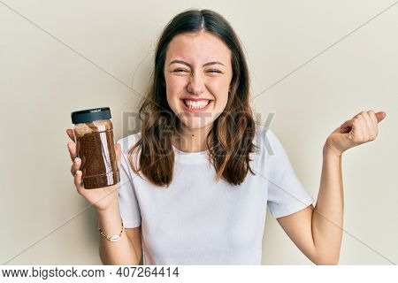 Young brunette woman holding soluble coffee screaming proud, celebrating victory and success very excited with raised arm
