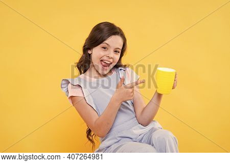 Drink It Baby. Happy Child Point Finger At Cup Yellow Background. Little Kid Enjoy Hot Drink. Milk T