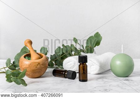 Natural Aromatherapy With Eucalyptus Essential Oil Bottles And Aromatic Bath Salts, Candle And Towel