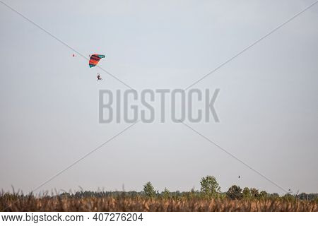 Orange And Green Parachute, Made For Two Persons, A Beginner And An Instructor, Falling Fro The Sky