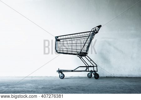 Shopping Cart In Front Of Supermarket Doorway For Customers Service, Empty Shopping Trolley In Front