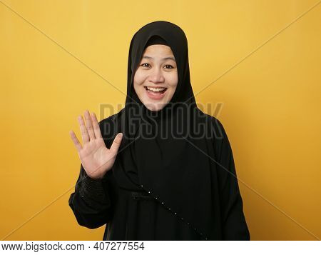 Portrait Of Muslim Woman Wearing Hijab Looking At Camera Smiling And Waving Her Hands Saying Hi Or G