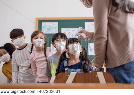 Teacher Using Digital Thermometer For Check Temperature On Asian Girl And Kid Foreheads. Diversity S