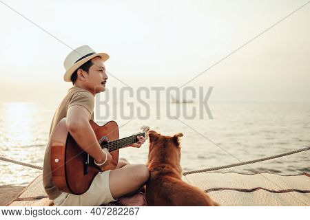 A Man Wear Straw Hat And Playing Guitar Music Song Near The Sea Sunset With A Dog Pet. Travel, Vocat