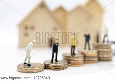 Miniature People:  Businessmen Shaking Hands On Coins Stack With House And Car.  Concept Of Investme