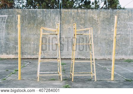 Yellow, Metal, Vintage Line Judge Chairs At Old Cement Outdoor Volleyball Court.