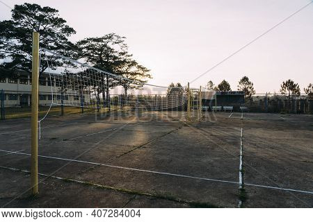 Old Beat-up Cement Volleyball Courts With Yellow Poles During Sunset In Dalat, Vietnam.