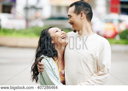 Happy Young Chinese Boyfriend And Girlfriend Laughing And Looking At Each Other When Standing Outdoo
