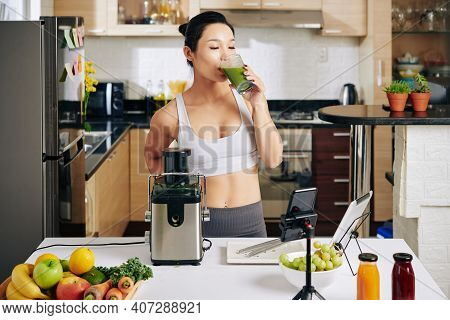 Fit Slim Female Athlete Standing In Kitchen And Drinking Glass Of Tasty Green Smoothie She Made For