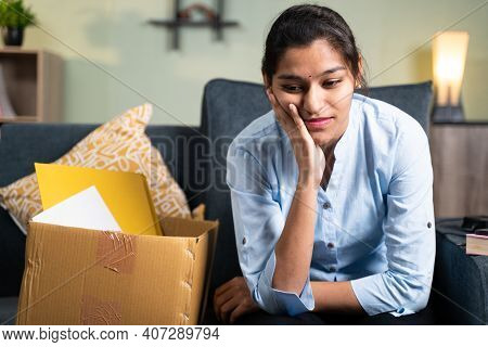Worried Young Business Woman Sitting Sadly On Sofa At Home Due To Loss Of Job, Employment Or Fired F
