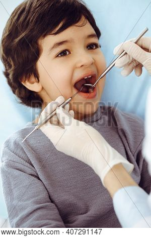 Little Arab Boy Sitting At Dental Chair With Open Mouth During Oral Checking Up With Dentist Doctor.