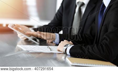 Businessman Using Tablet Computer And Work Together With His Colleague In Sunny Modern Office, Close