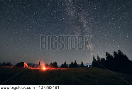 Male Hiker Standing Near Campfire And Tent Under Beautiful Night Sky With Stars. Magnificent View Of