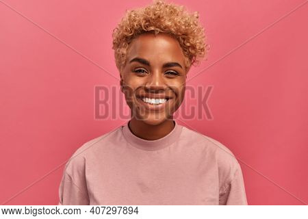 Studio Portrait Of Young Dark Skinned Woman With Blonde Hair In Good Mood Standing On Pink Backgroun