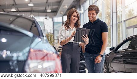 Positive Young Professional Saleswoman Demonstrating Document To Male Customer Buying New Car In Dea