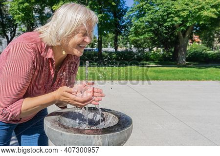 Mature Woman Refreshing From Drinking Water Fountain On Hot Summer Day. Blond Woman Splashing Water