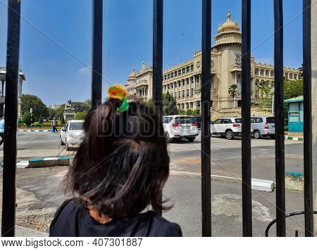 Closeup Of Indian Kid Watching Famous Vidhana Soudha Building From The Big Iron Gate Gap