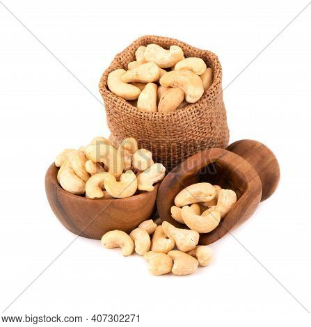 Cashew Nuts In Bag And Wooden Bowl, Isolated On White Background. Roasted Cashew Nuts.