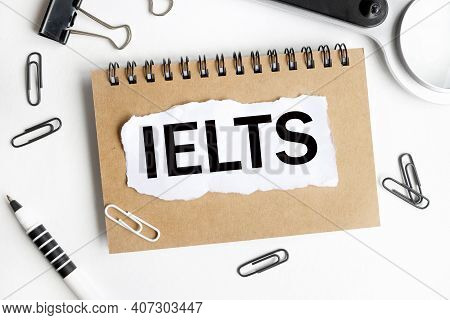 Ielts.text On White Paper Over White Background. Notebook, Pen.