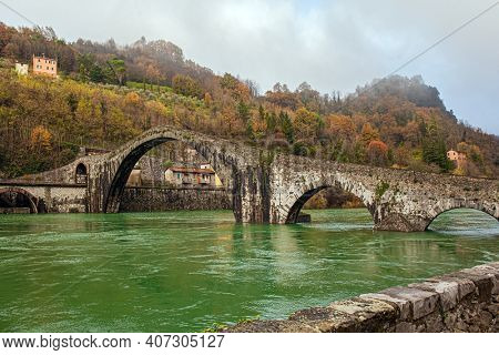 Cold green waters of the Sercchio River. Italy. Province of Tuscany. The vicinity of the city of Lucca, Ponte della Maddalena Bridge. Bridge built a thousand years ago. Cold windy winter day
