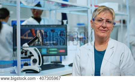 Portrait Of Old Scientist Woman Smiling At Camera In Modern Equipped Lab. Multiethnic Team Examining