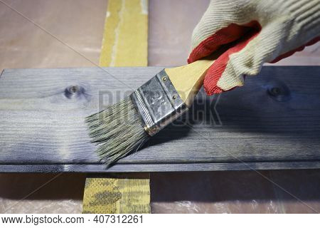 Handling A Woody Pine Plank With A Dark Mordant With A Paintbrush For Deeply Impregnating Wood For P