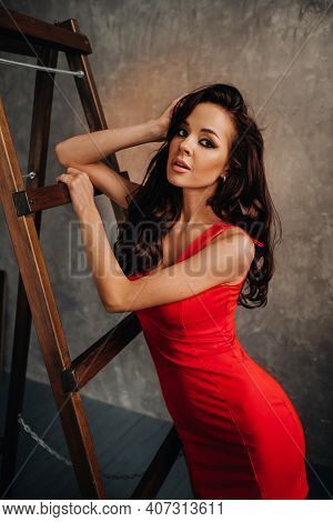 A Brunette With Long Hair In A Red Dress Poses In The Studio Near The Stairs
