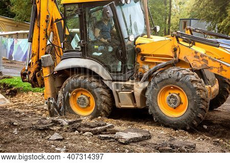 A Heavy Yellow Road Excavator Performs Earthworks On A Construction Site.