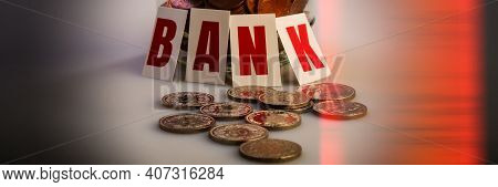 Inscription Bank In Block Letters And Coins Lie On A Blurred Background. Web Banner.