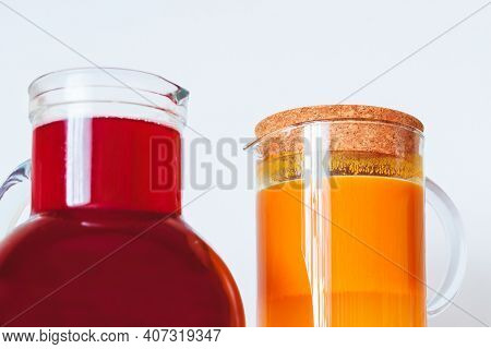 Two Jugs Of Berry Juice. Sea Buckthorn Juice And Juice From Different Berries.