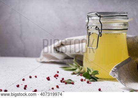 Selective Focus. Homemade Beef Bone Broth In A Glass Jar. On A Light Gray Background. With The Addit