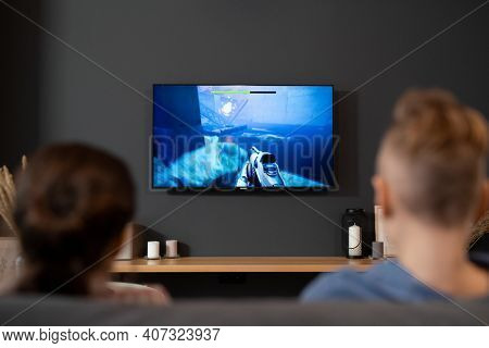 Back view of two contemporary siblings sitting in front of tv set and playing video game in living-room during vacations or on weekend