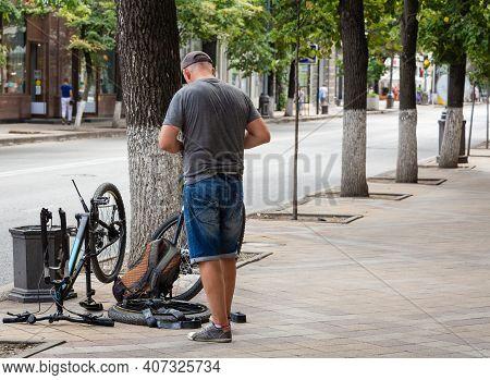 Krasnodar, Russia - August 20, 2020. Bicycle Repair. A Man Repairs A Bicycle Wheel In The Street.