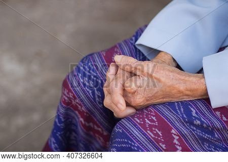 Close-up Of Hands Senior Woman Joined Together While Sitting On A Chair In A Garden. Focus On Hands