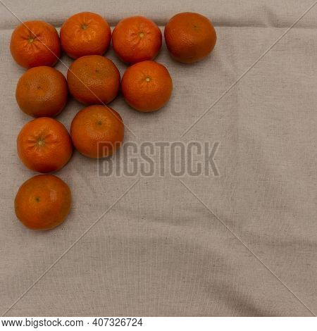 Ripe Tangerines Lie On A Beige Napkin. The Fruits Are Laid Out In A Triangle Shape In The Upper Left