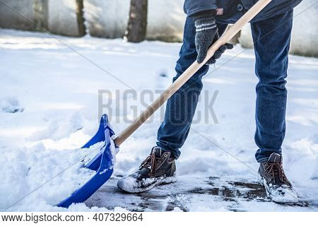 A Horizontal View Of Shoveling Snow From A Sidewalk With A Snow Shovel.