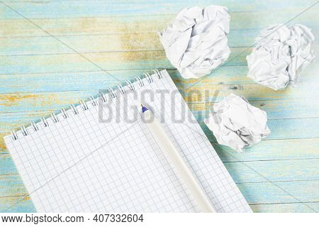Empty Notebook With Pen And Crumpled Paper Balls On Wooden Table, Flat Lay. Space For Text