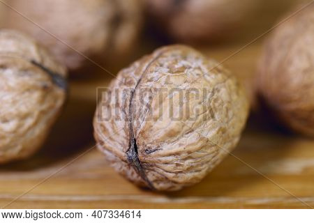 Food Background. Walnut Close-up. Round Whole Walnuts Lie On A Wooden Table.