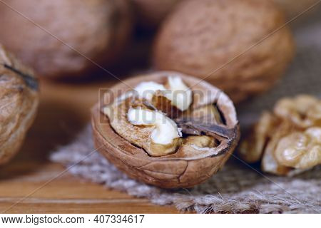 Food Background. Walnut Kernels Close-up. Chopped Nuts Lie On A Wooden Table.