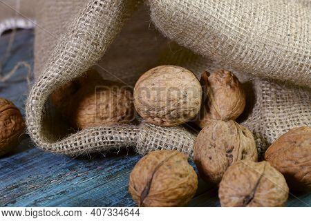 Food Background. Whole Walnut Close-up. A Round Walnut Spilled From A Sack On A Blue Wooden Table.